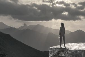 Woman standing on rock outcropping looking a mountain view