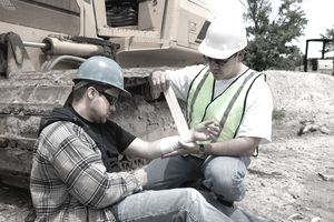 Worker on a construction site bandaging another worker's arm after an injury.