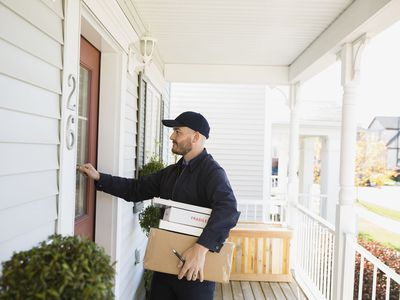 Postal Delivery Man With Parcels Knocking on Door