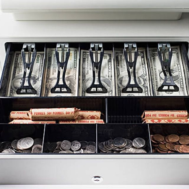 Open cash register containing bills, loose and rolled coins