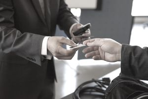 Close-up of men's hands exchanging business cards