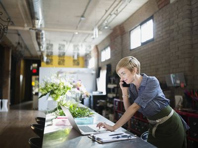 Woman working at kitchen counter on laptop and phone