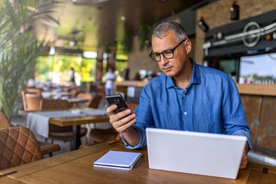 Restauraunt owner reviewing business financials on his computer and smartphone