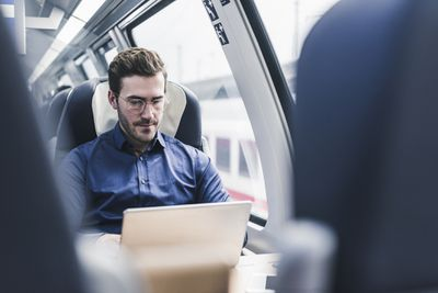 Man with glasses using laptop on a train
