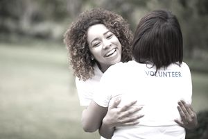 Young volunteers hugging.