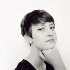 Image of the writer in black and white. They have short hair, are wearing a black jersey tshirt and resting their chin on their hand. Hannah is looking at the camera with a resting, neutral face.