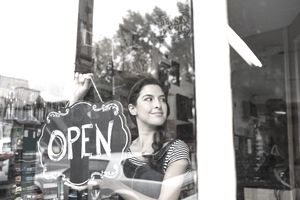 Confident small business owner hanging Open sign in shop window