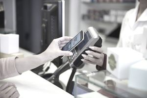 A cashier holds up a payment terminal to interface with a smartphone and payment is made, without cash.