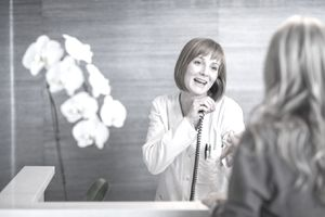 Dental receptionist greeting client while also talking on the phone