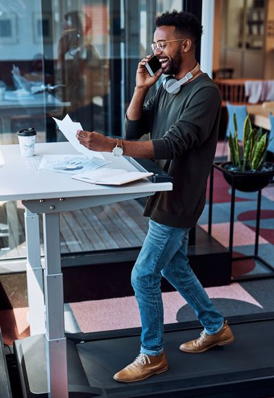 A young businessman talking on a cellphone and going through paperwork while walking on a treadmill in an office