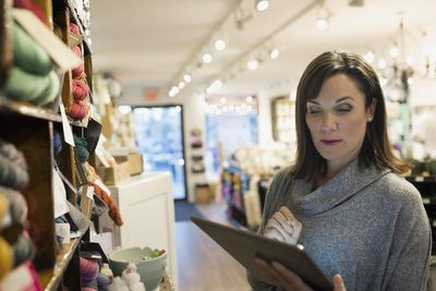 Yarn store owner taking inventory with digital tablet