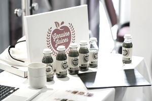 Start up juice company logo on table with juice bottles at a trade show.