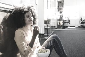 Young woman enjoying snack at the office
