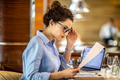 Female entrepreneur reading a paper document while sitting in a restaurant. She is holding her reading glasses. A laptop, a clipboard, a water glass and a bottle are on the table.
