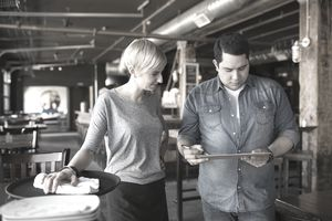 Pub owner and server looking at clipboard