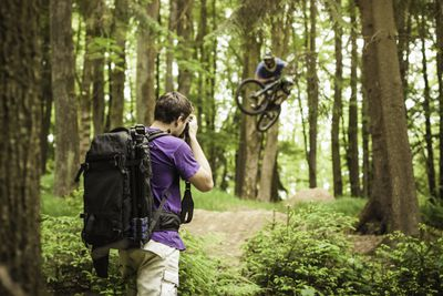 Young Male Photographer Photographing Mountain Biker In Forest