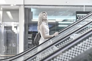 Woman going up an escalator