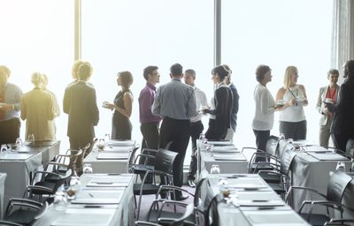 Group of people standing by windows of conference room, socializing during coffee break
