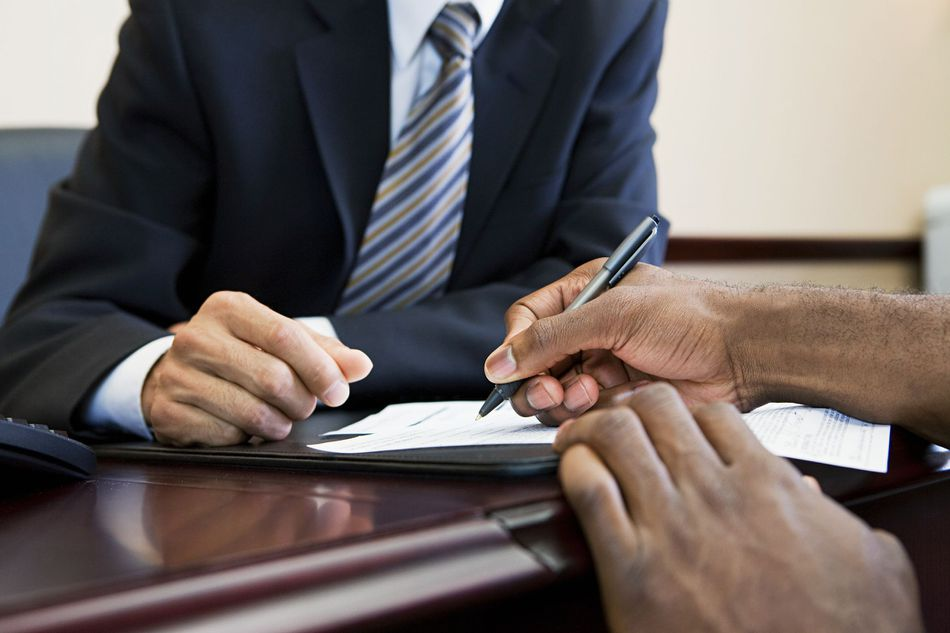 Man signing document in front of banker