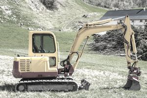 small excavator in alpine landscape