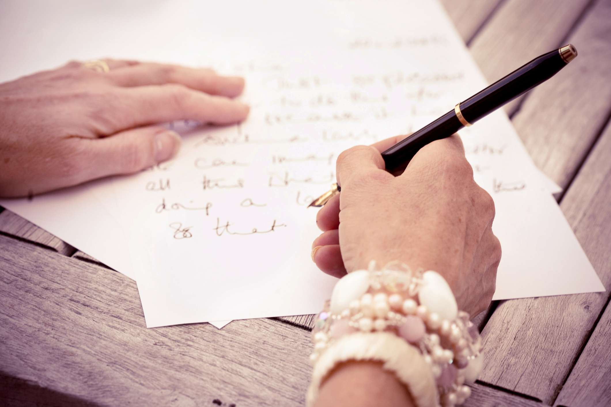 Close up of hands writing a thank you letter