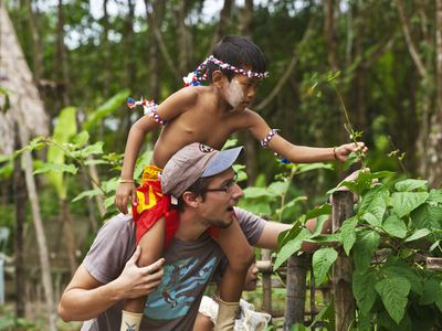 A western volunteer gives a ride to a Thai boy in the ORGANIC GARDEN at the HOME AND LIFE ORPHANAGE in PHANGNGA - KHAO LOK, THAILAND