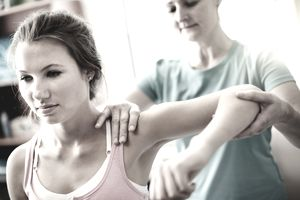 A young woman is receiving physical therapy from a female therapist.