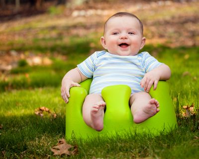 Happy baby using training Bumbo seat to sit up that the parent bought on eBay