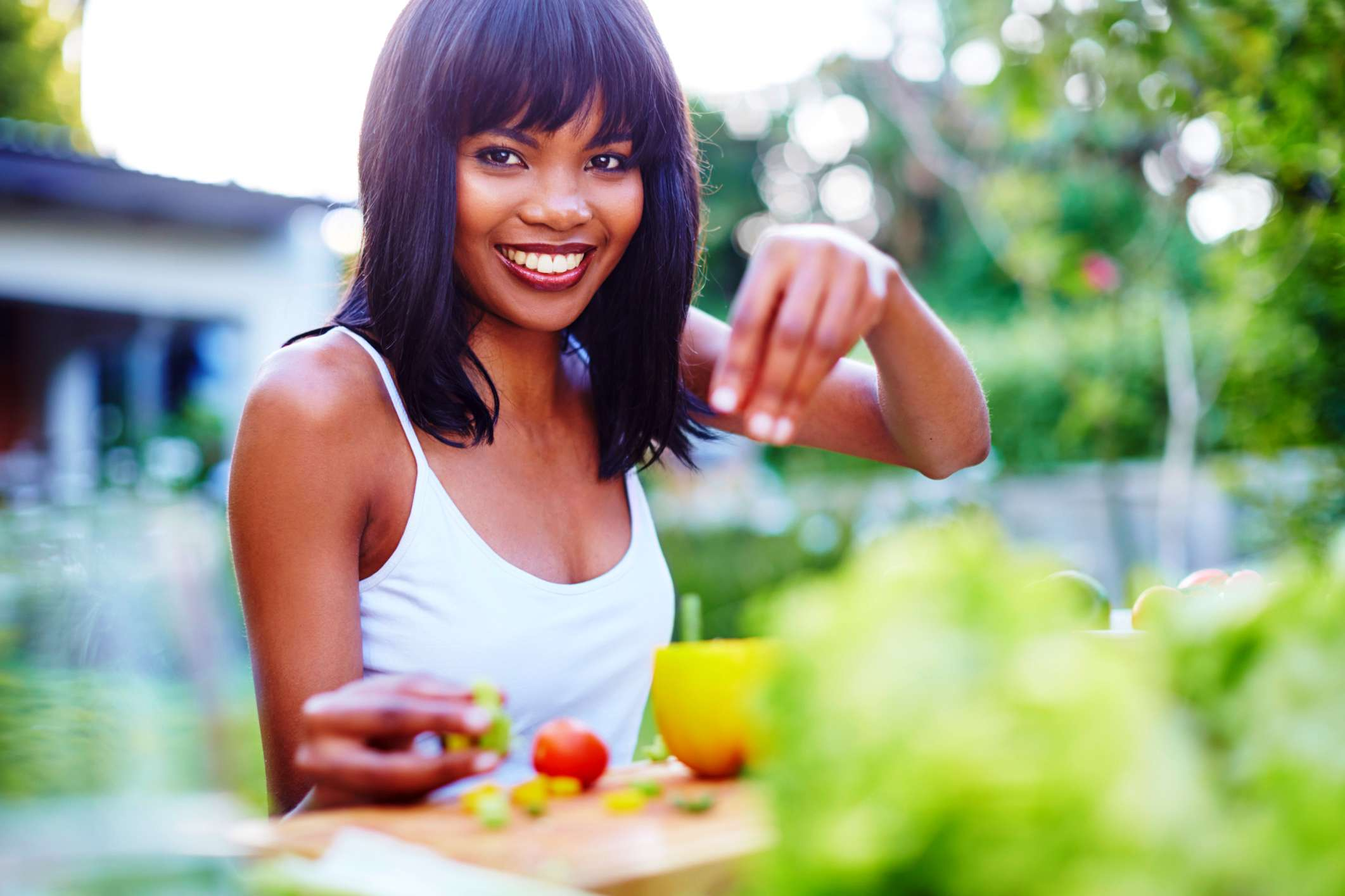 Smiling woman eating fresh garden vegetables and drinking tea outside