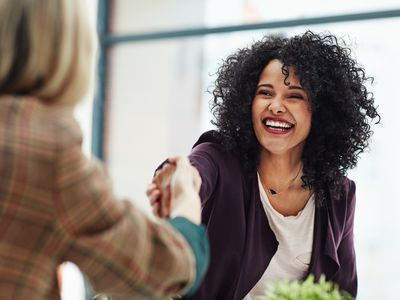 Smiling woman shaking hands with another woman.