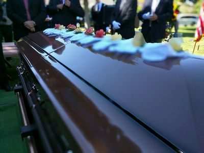Close-Up Of Decorated Coffin Against Men At Funeral