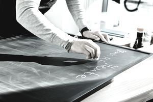 Worker writing on restaurant chalkboard