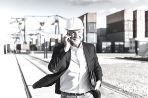 Importer talking on his cellphone at a shipping dock.