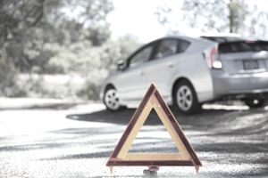 Car at roadside behind warning triangle