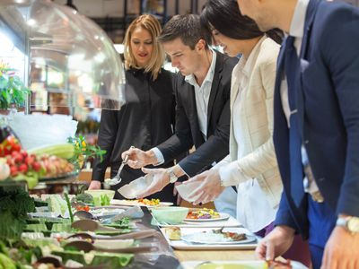 People serving themselves on a catered buffet line at an event.