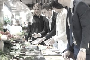 Four people serving themselves from a buffet table