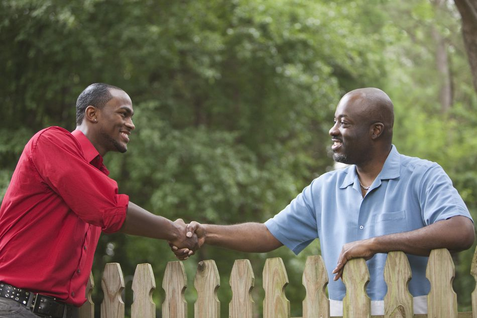 African American neighbors greeting each other over fence