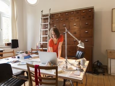 a young female designer working in a home office