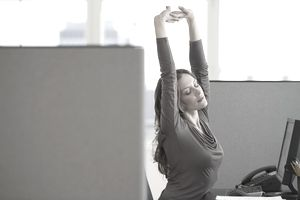 Woman stretching at her office desk