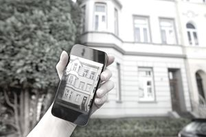 a hand holding a phone showing a pic of a building