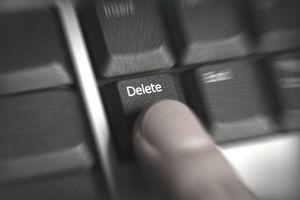 a finger pressing the delete key on a keyboard