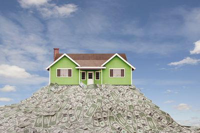A model of a house sitting on top of a pile of crowdfunding cash