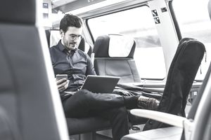 Businessman working in train using laptop