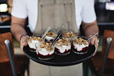 Midsection of owner holding dessert in tray while standing at counter in restaurant