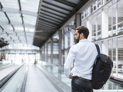 Business man on moving walkway wearing a backpack