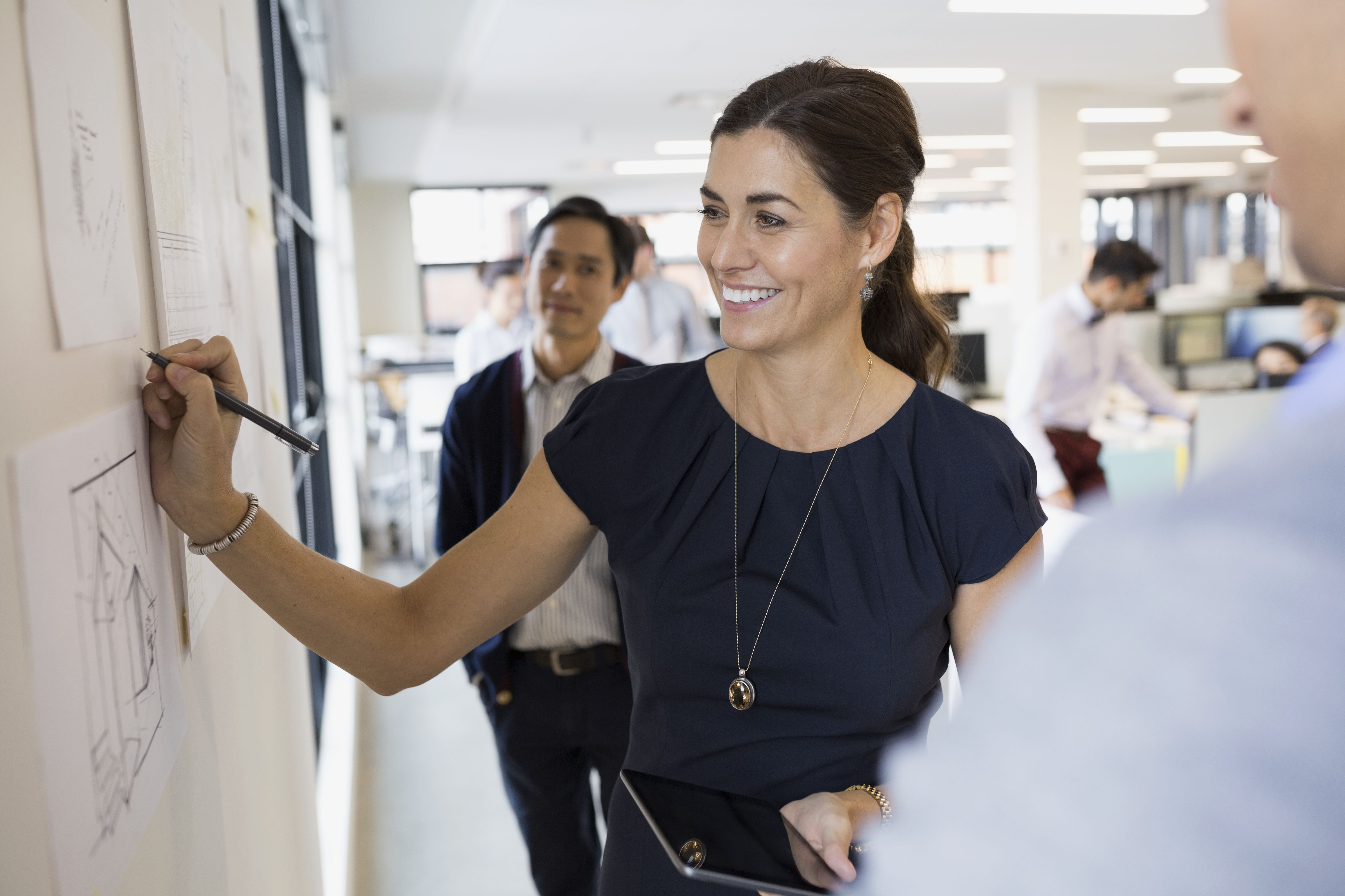 Professional-looking woman leading a team meeting at a white board