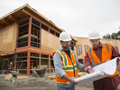 Two workers on a construction project site reviewing building plans