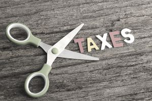 Scissors With TAXES Word on Wooden Background