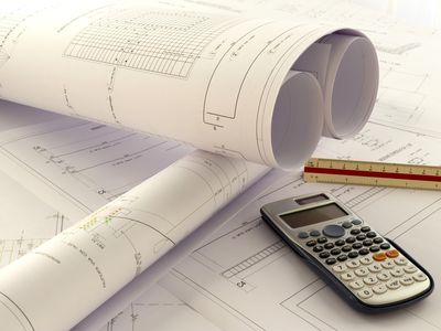 High Angle View Of Calculator With Ruler And Blueprints On Desk