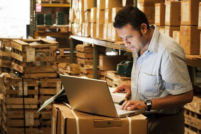 Worker taking inventory in a warehouse using his laptop